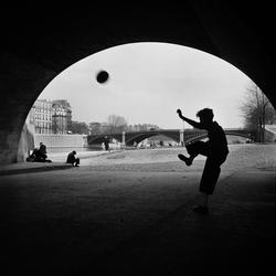 Paris. En pojke sparkar fotboll under en bro.