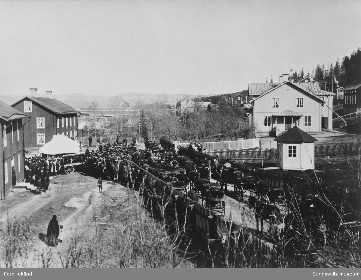Stor begravningsprocession i Skönviks sågverkssamhälle. Flaggorna vajar på halvstång och en stor skara människor har slutit upp. Likvagnen står uppställd till vänster med många män med höga hattar invid. En tältliknande byggnad står upprest intill. Följet är på väg ner mot vattnet vilket tyder på att den döde ska fraktas iväg. Den avlidne kan ev. vara Fredrik Bünsow eftersom han avled i september 1897 och begravningståget gick mot hamnen för vidare färd med båt mot Stockholm där han ligger begravd.