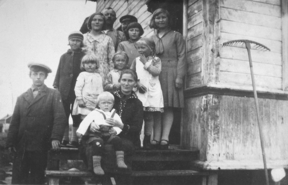 Flere personer poserer på en trapp til et hus som sansynligvis står i Kvalsund kommune før evakueringa. Personene er ukjent, men det er muligens en familie.