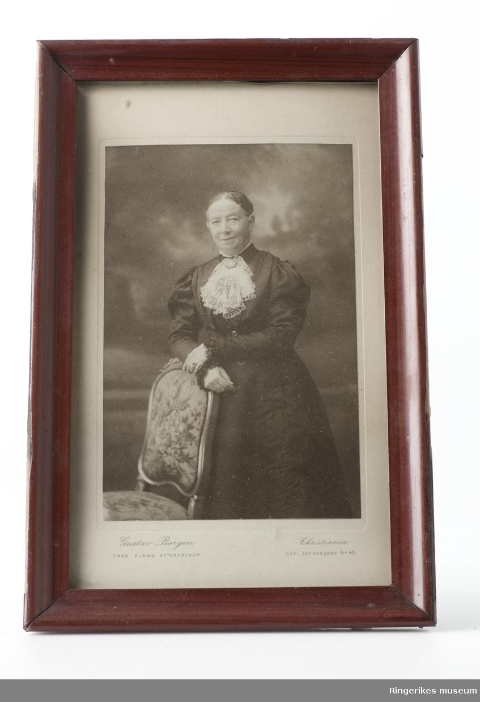 Bisbinde Sofie Moe fotografert hos Gustav Borgen i Christiania. Bildet viser Sofie stående med armen hvilende på en stol.
