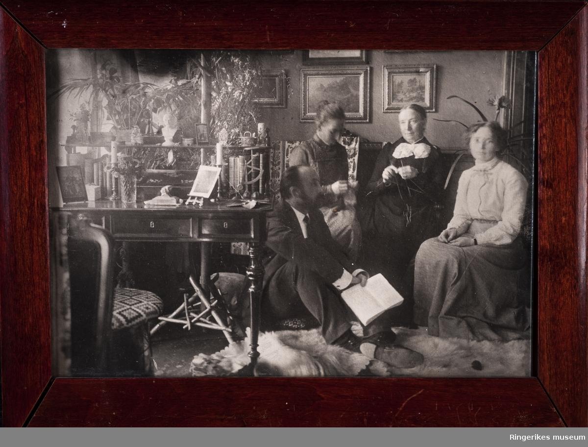 Familiebilde av Sofie, Moltke, Marie og Aleksandra Moe. Avbildet i en stue med skrivebord, stol og sofa. Bilder på veggen etc. Sofie strikker. Det gjør også en av jentene. Moltke holder en bok.