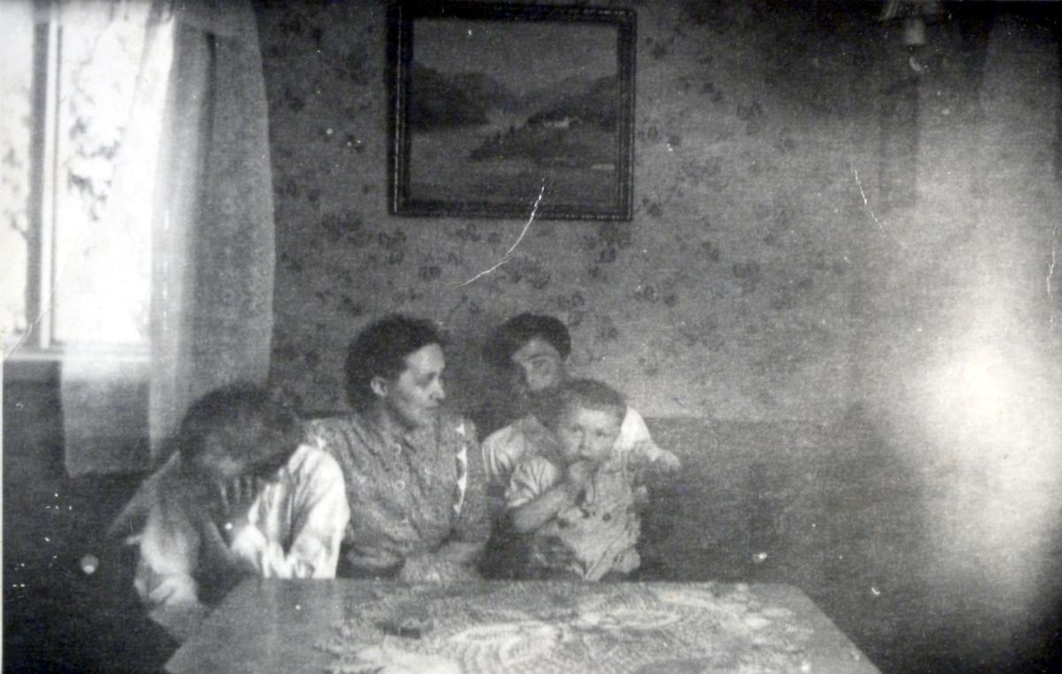 Fire personer fotografert i en stue, muligens i Kvalsund kommune før evakueringa. Personene er ukjent.