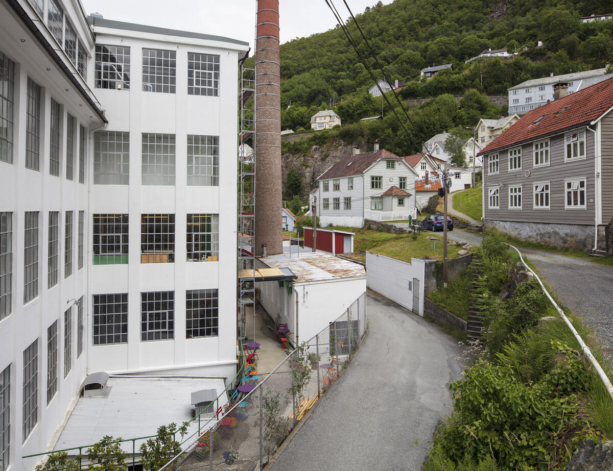Bygda Salhus utanfor Bergen, med den tidlegare tekstilfabrikken Salhus Tricotagefabrik, fabrikkpipa og ein arbeidarbustadtil høgre. (Foto/Photo)