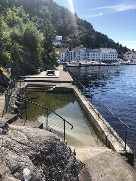 Utandørs basseng ved sjøen, utsikt til fabrikk i bakgrunnen (Foto/Photo)