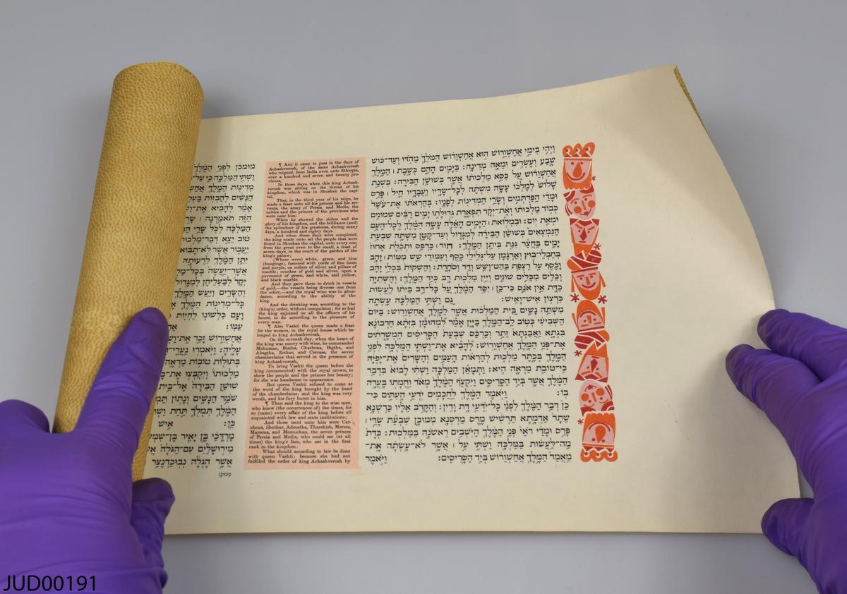 """Megillat Ester liggandes i blått fodral, som i sin tur ligger i en vit pappkartong. Lådan är dekorerad med blå text (hebreisk och engelsk), samt blåa linjer. Fodralet är dekorerat med guldig text där det står """"The book of esther. With the compliments of the ministry of tourism. Jerusalem Israel. Specially printed for our guests from abroad. Purim, 5727 (1967)"""", samt med vita linjer i båda ändar.  Själva rullen är på utsidan dekorerad som att se ut som hud. Rullen är skriven på hebreiska, med infällda engelska textrutor. Rullen är inuti dekorerad med målade ansikten i olika röda nyanser i rullens början och slut"""