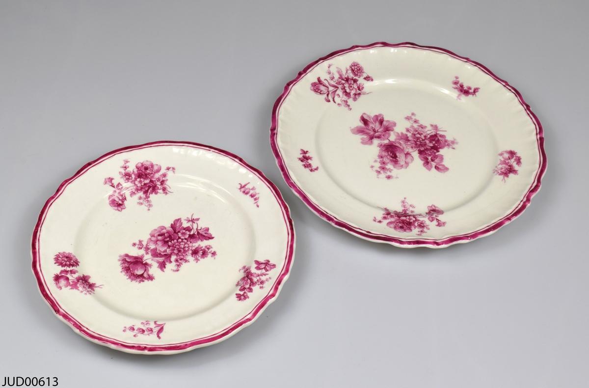 Två porslinstallrikar av olika storlek. Båda är likadant dekorerade med rödrosa blommor. Tillverkade av Rörstrand, enligt stämpel i botten.