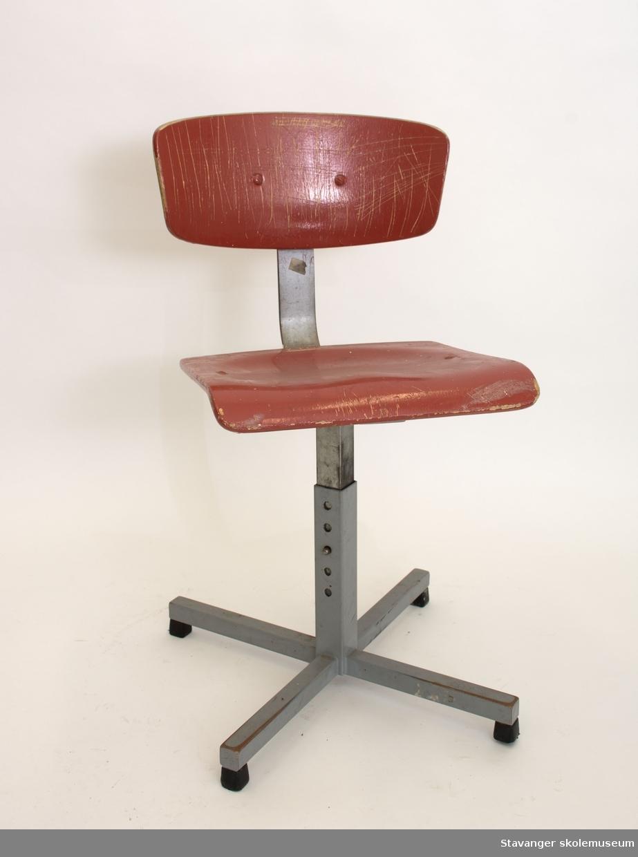 Elevstol av jern og bøyd kryssfiner. Gråmalt stål og rødmalt kryssfiner i sete og rygg. Er justerbar i høyde.