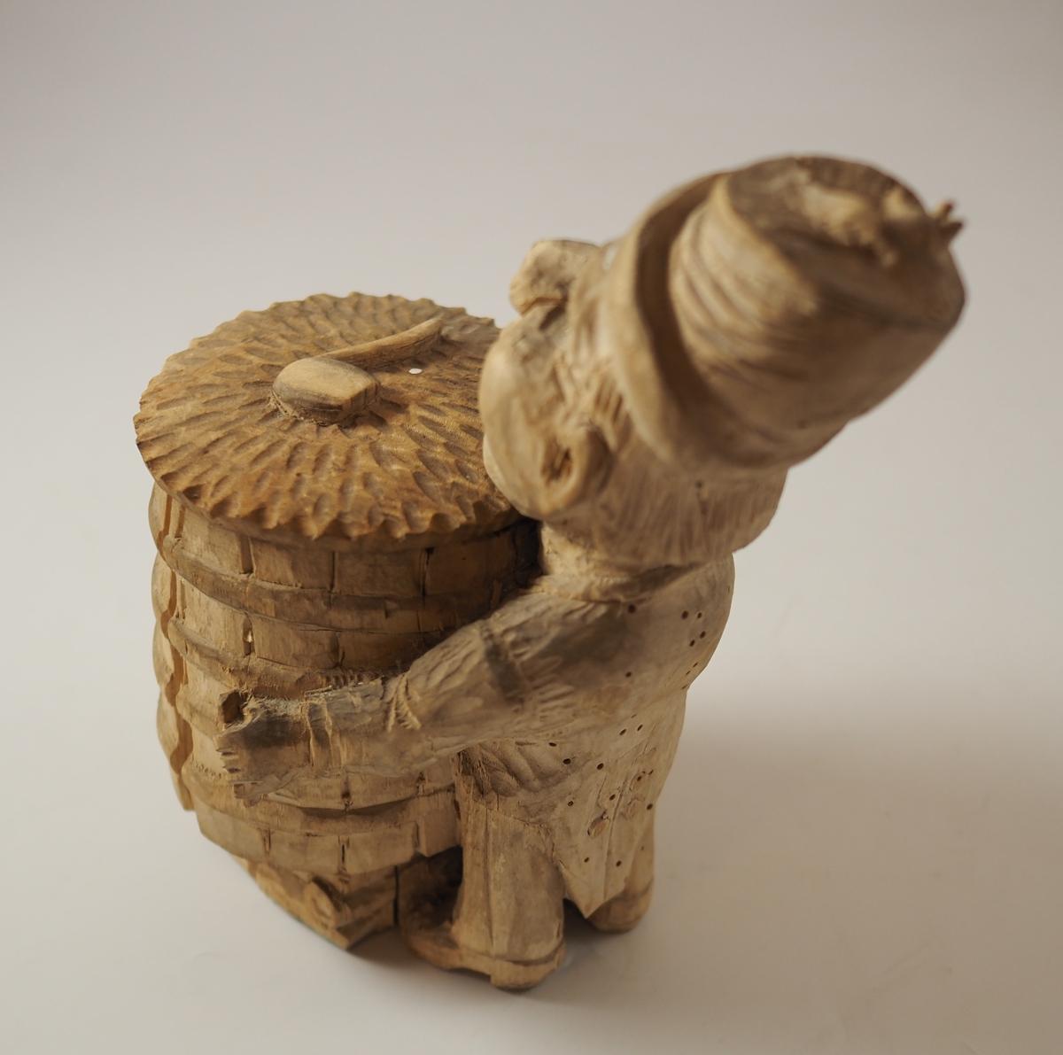 Mann og krukke skåret i tre med grove, enkle redskaper. Ei pipe er skåret på lokket til krukka. I hatten til mannen sitter ei mus. Inskripsjon risset inn under figuren.