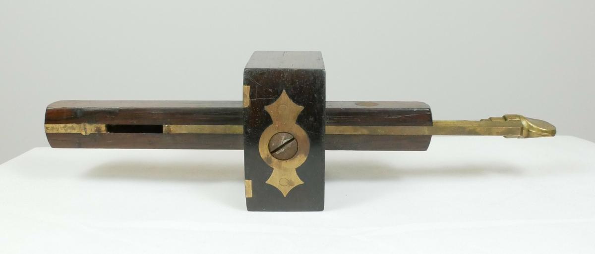 Rektangulær strekmåler i tre med metallbeslag. Består av en firkantet trestykke med et rektangulært trestykke imellom. På det rekstangulære trestykke er det to metallpigger, øverst er det en gjenget del med en del som kan brukes til å skru.   Påskrift:  J. TYZACK & SON // SHEFFIELD ENGLAND
