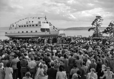 Svart-hvitt foto av ferje pyntet med flagg og en stor folkemengde.. Foto/Photo