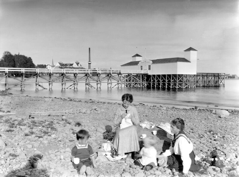 Svart-hvitt foto av to kvinner og to barn som sitter på en steinete strand ved Mjøsa. Hamar badehus i bakgrunnen. (Foto/Photo)