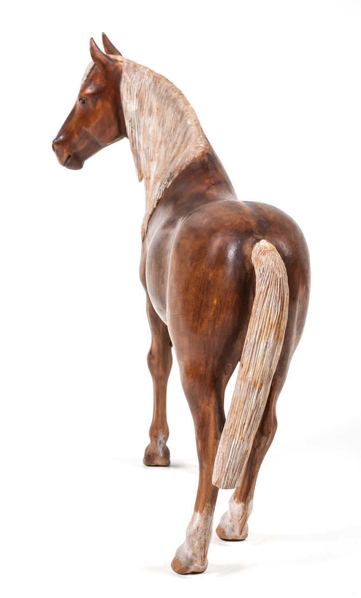 """Träskulptur """"Häst"""" av Lars From (1867-1945) från Hälsingland. Naturalistisk häst. Brun med vit man och svans. Vita strumpor på bakbenen. From brukar signera sina hästar med initialerna LF på någon av de bakre hovarna. Denna häst verkar vara osignerad."""