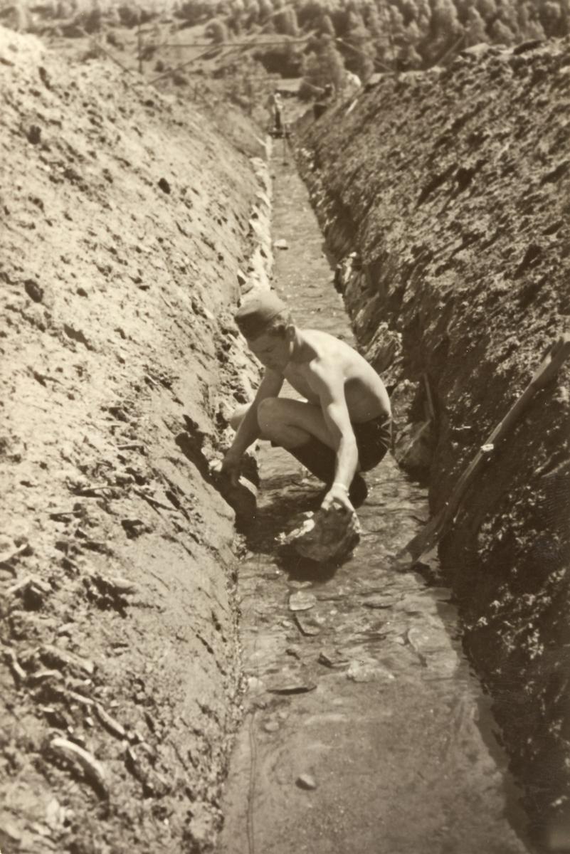 En mann arbeider på en vanningskanal. Kanalen i senter av bildet, 1 mann i bar overkropp med  militærlue arbeider på i bunnen av kanalen. Skogkledd åsside.
