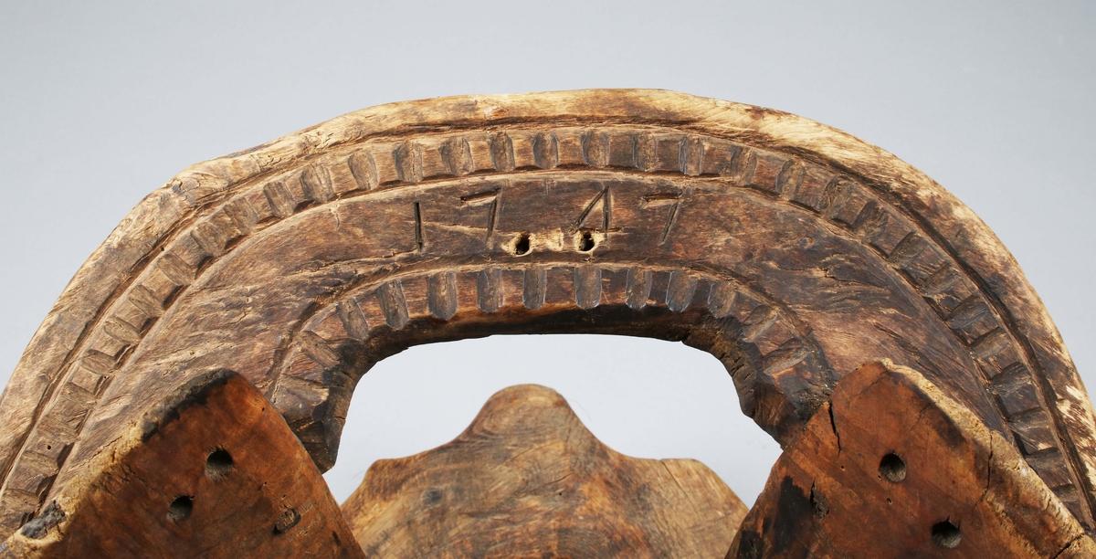 Klövjesadel för häst. Fram- och bakstycke med sniderier. Användes för transport av diverse varor.  Äldre registerkort: Träställ. På frambomens överkant järnöglor. Kvarsittande linstumpar. Grovt snidad. På bakbomen skuret: 1747