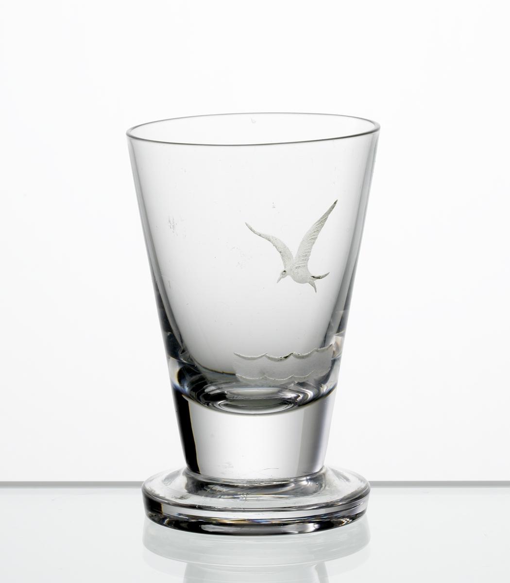 Design: Edward Hald. Brännvinsglas. Konisk kupa på fot. Graverad mås och vågor på kupan.