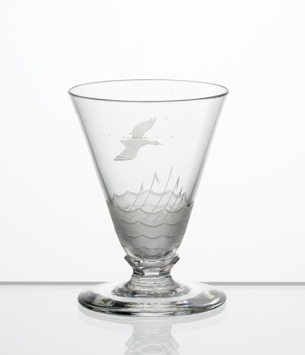 Design: Edward Hald. Brännvinsglas. Konisk kupa med fasettslipad knapp mellan kupa och fot. Graverad flygande andfågel och, på kupans nedre del, vass och vatten i vågor.