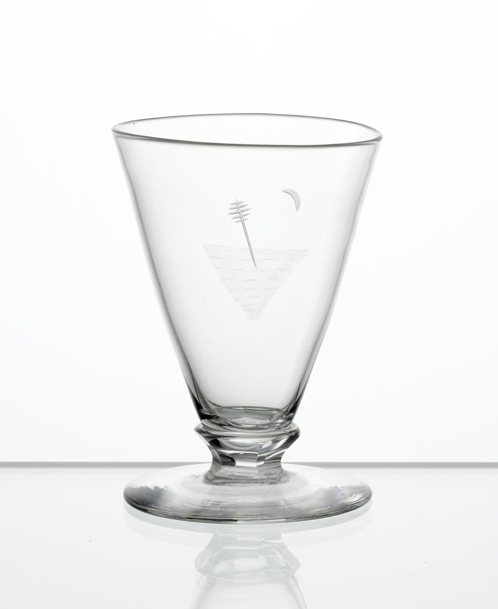 Design: Edward Hald. Brännvinsglas, konisk kupa med graverat motiv bestående av sjömärke. Fasettslipad knapp mellan kupa och fot.
