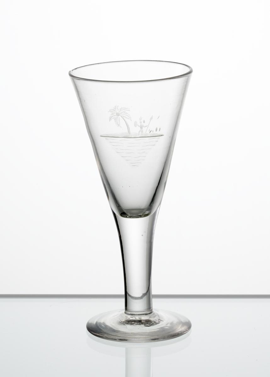 Design: Edward Hald. Brännvinsglas, konisk kupa. Graverat söderhavsmotiv bestående av palm och inföding med spjut och sköld på kupan.