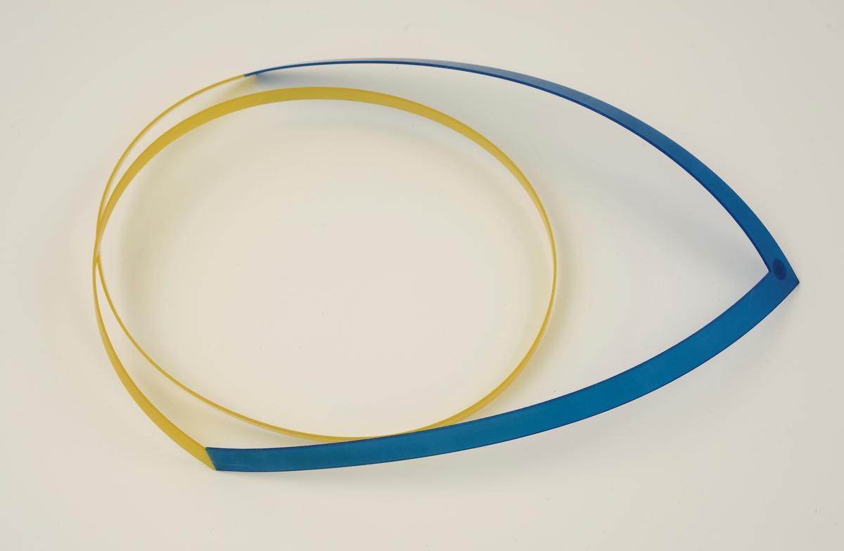 Halssmykke laget av stive nylonbånd som er cirka 1 cm brede. Foran er det et v-formet bånd i blå nylon, til dette er det festet et gult bånd som slynger seg i en spiral.
