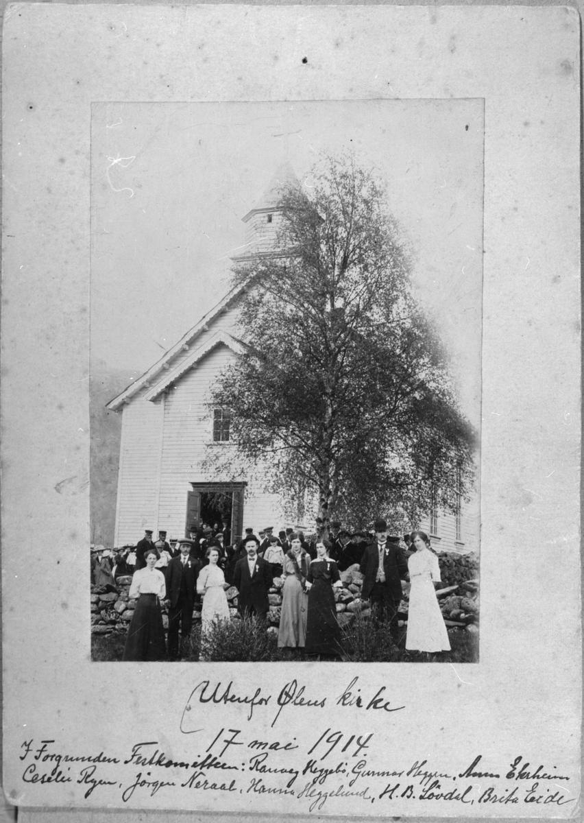 Ølen kyrkje under grunnlovsjubileet, 17. mai 1914. I forgrunnen er festkomiteen. Frå venstre: Ranveig Heggebø, Gunnar B. Heggen, Anna Ekrheim, Jørgen Nerål, Sesilie Ryen, Hanna Heggelund, Hans B. Løvdahl og Brita Eide.