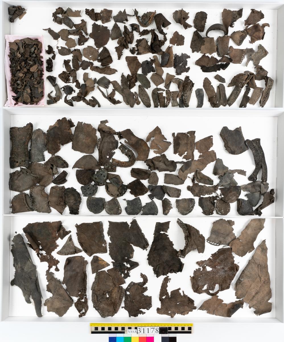 Runt 400 delar och fragment från skor i form av sulor, inlägg, ovanläder, klack, sidostycken, bakkappor, träpliggar, tråd mm. Troligtvis rör det sig om delar och fragment från flera skor och/eller stövlar. Delar av lädret har förstärkts med lim av konserveringsenheten. Merparten av lädret är spaltat samt har hål efter träpligg eller stygn.