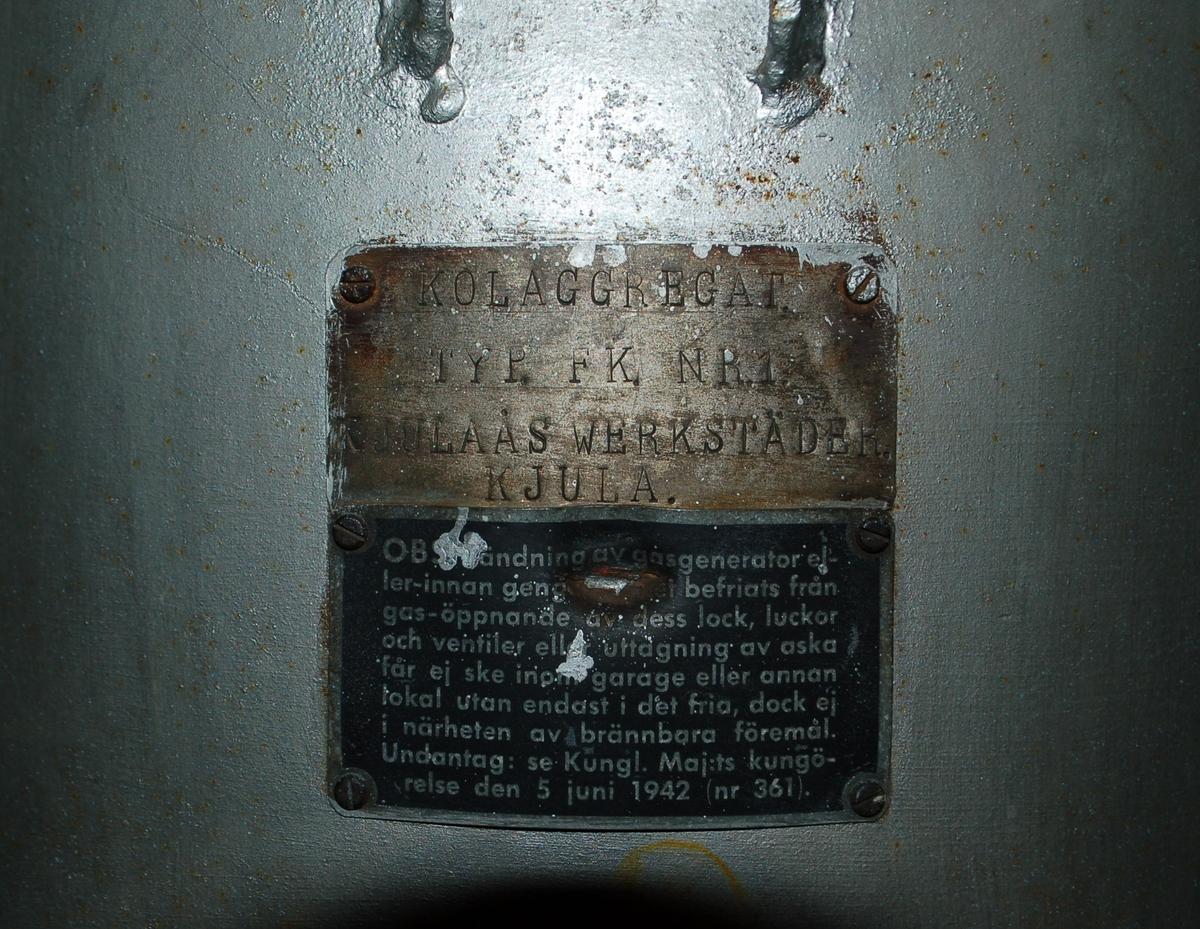 Silvermålat gengasaggregat för kol, bestående av en stor tunna för ved och eldning, samt rör kopplade till två mindre tunnor för gasframställning. Skylt: Kolaggregat, typ Folke Karlsson nr 1, Kjulaås Werkstäder, Kjula.  På aggregatet sitter en varningsskylt som bl a hänvisar till Kungl Maj:ts kungörelse 5 juni 1942/nr361.  TYP: FK nr 1 TNR: 1997