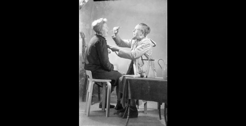 """""""Doktor som undersøker kvinnelig pasient"""". Arrangert humoristisk fotografi.  Fotografering 1930 - 1940 Østerike, Gardermoen. (Foto/Photo)"""