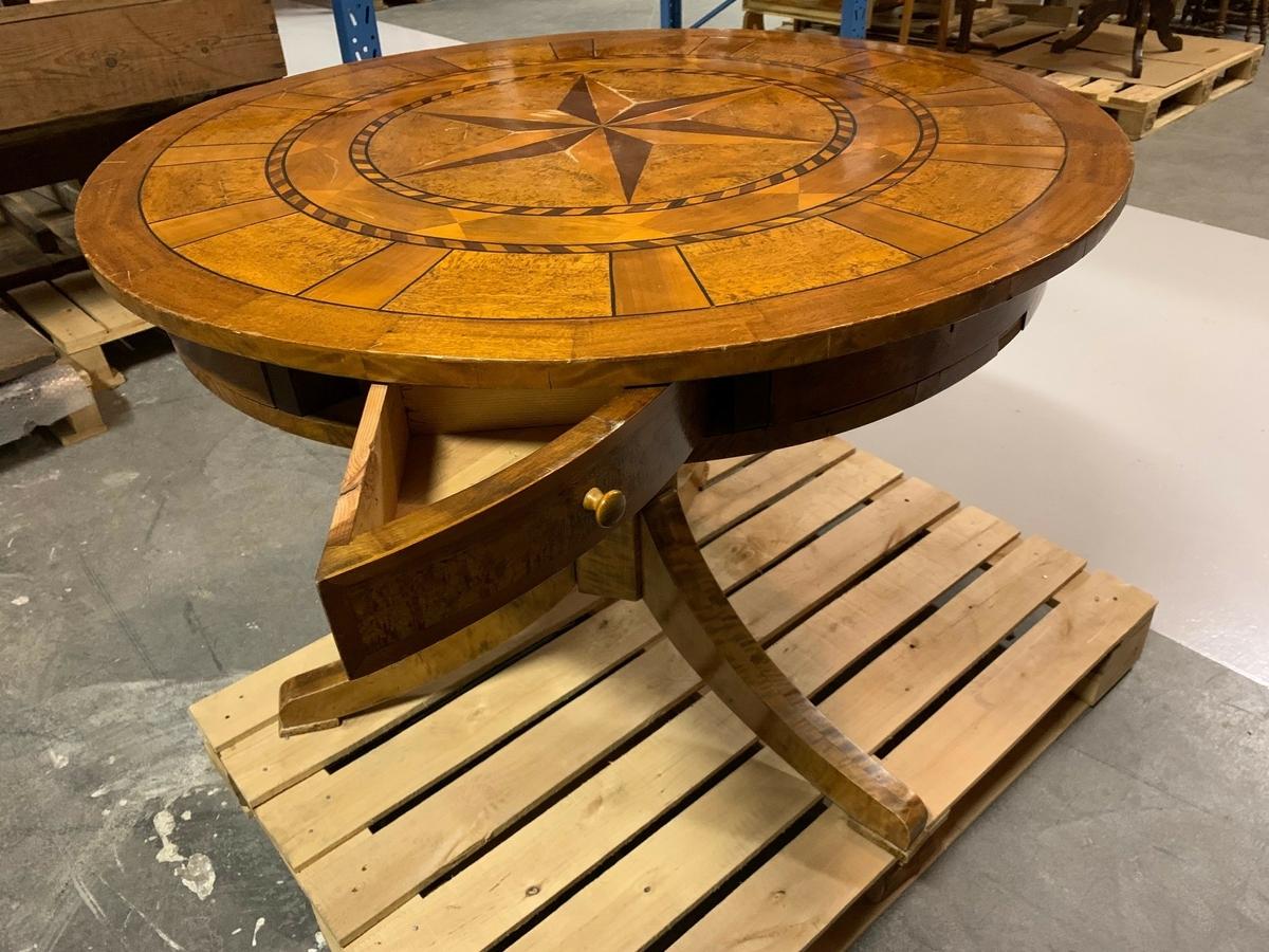 Runt bord med svängbar skiva på kullager. Inläggningar av svenska träslag (intarsia). Trekantiga, utvikbara/utfällbara lådor i sargen. Sexkantigt centrerat bordsben med tre utsvängda fötter.