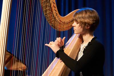 Kvinne som spiller harpe. Foto/Photo
