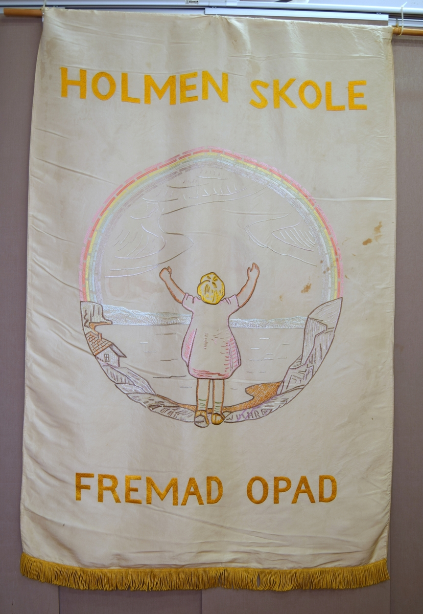 På forsiden: En jente i kort kjole står med armene i været og ser ut over sjøen. En regnbuen danner halvparten av en sirkel med himmelen. Den andre halvparten er med et landskap med et hus på venstre side. På baksiden et kors i en stilisert blomsterramme.