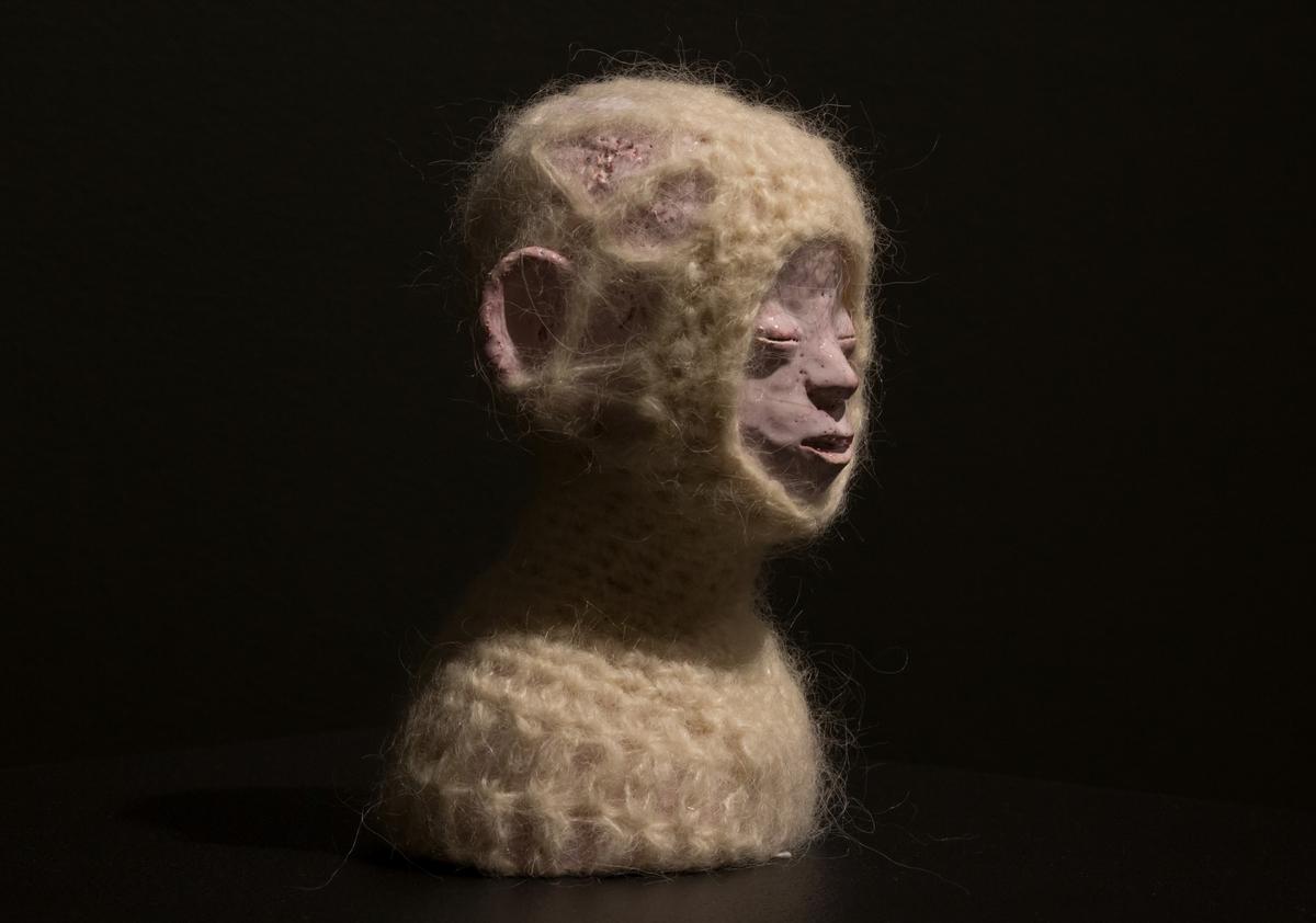 Byst av figur med stängda ögon iklädd en stickad dräkt som täcker allt utom öron och ansikte.