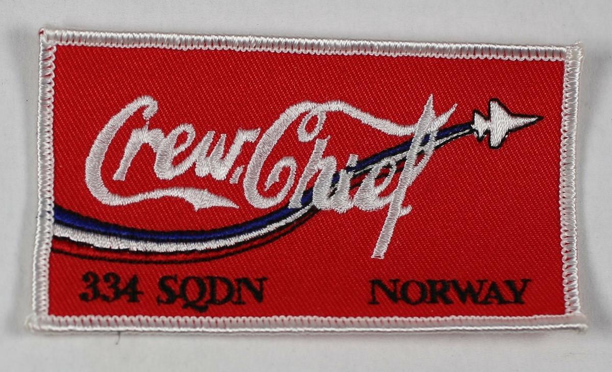 """Rødt firkantet merke med hvit skrift. """"Crew chief"""" er skrevet med samme font som Coca Cola. Dette er sannsynligvis gjort fordi COLA var kallesignalet til 334 skvadron når de fløy F-104 og F-16."""