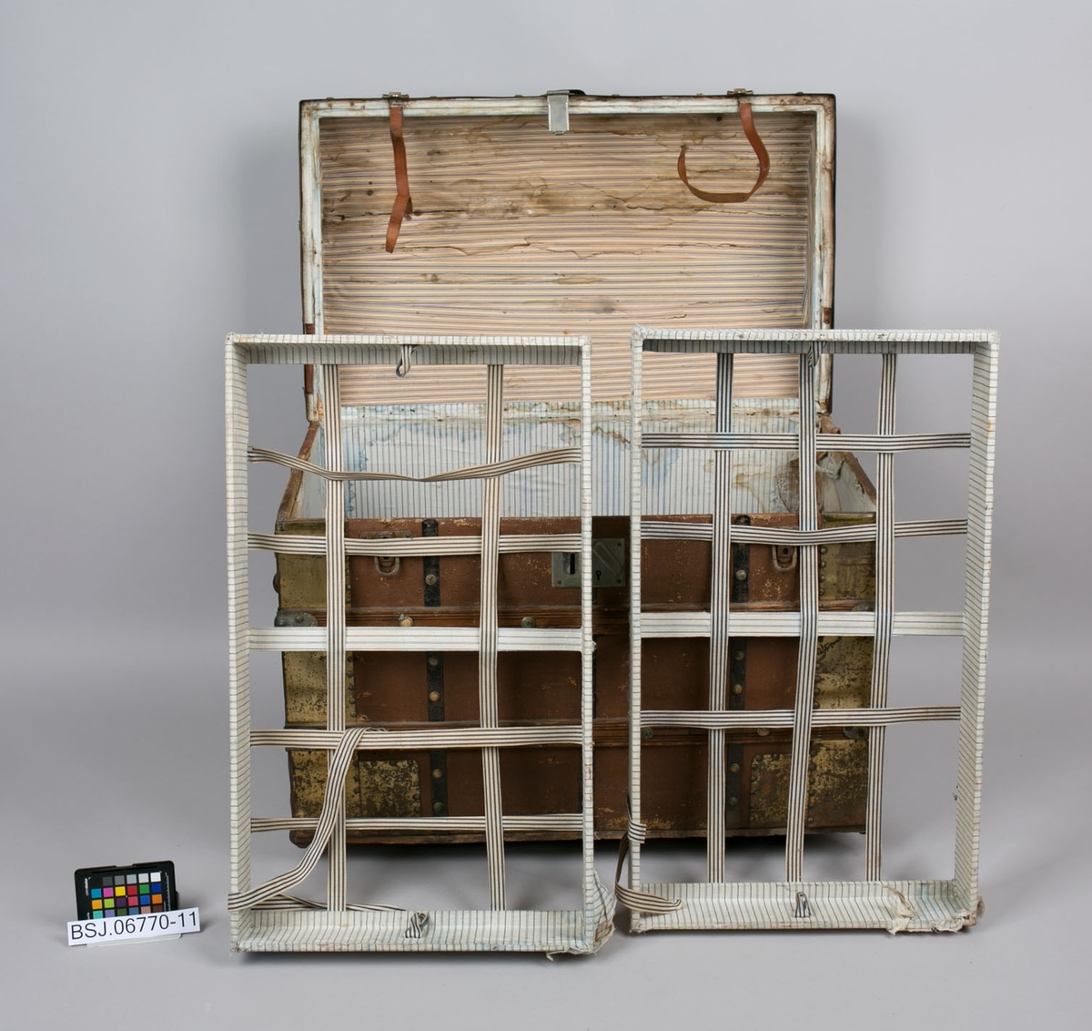 Kiste i tre med buet lokk. Beslag i metall og trukket med hempestoff. Inni er det to innlegg for klesoppbevaring, i tre trukket med hvit og blåstripet bomullsstoff. Bunnen av disse består av tekstilreimer.