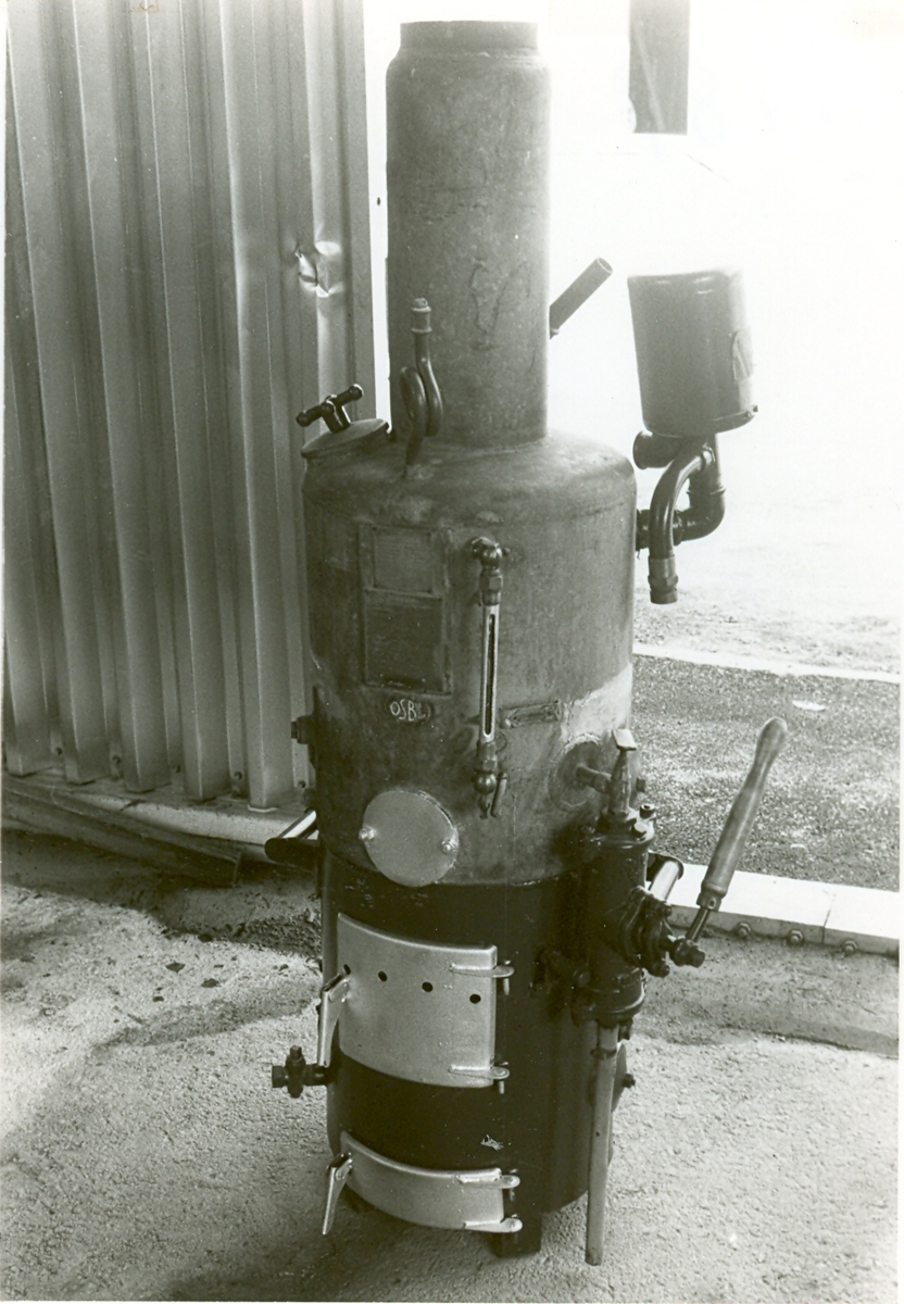Delvis grönmålad ångpanna, med silverfärgade luckor. Toppen i galvaniserad plåt. Stående lågtryckspanna Osby Special. Ångtryck 0,5 kg(kvcm, kalltryck 2 kg/kvcm, eldningsyta 1,9 kvm. Skylt Vfn i F län.  Tillverkare: AB Vattenvärmare-kompaniet, Osby.   Modell: 47 Osby Maskinnr: ÅL 4 Typ: 11 År: 1947 Tillv nr: H2647
