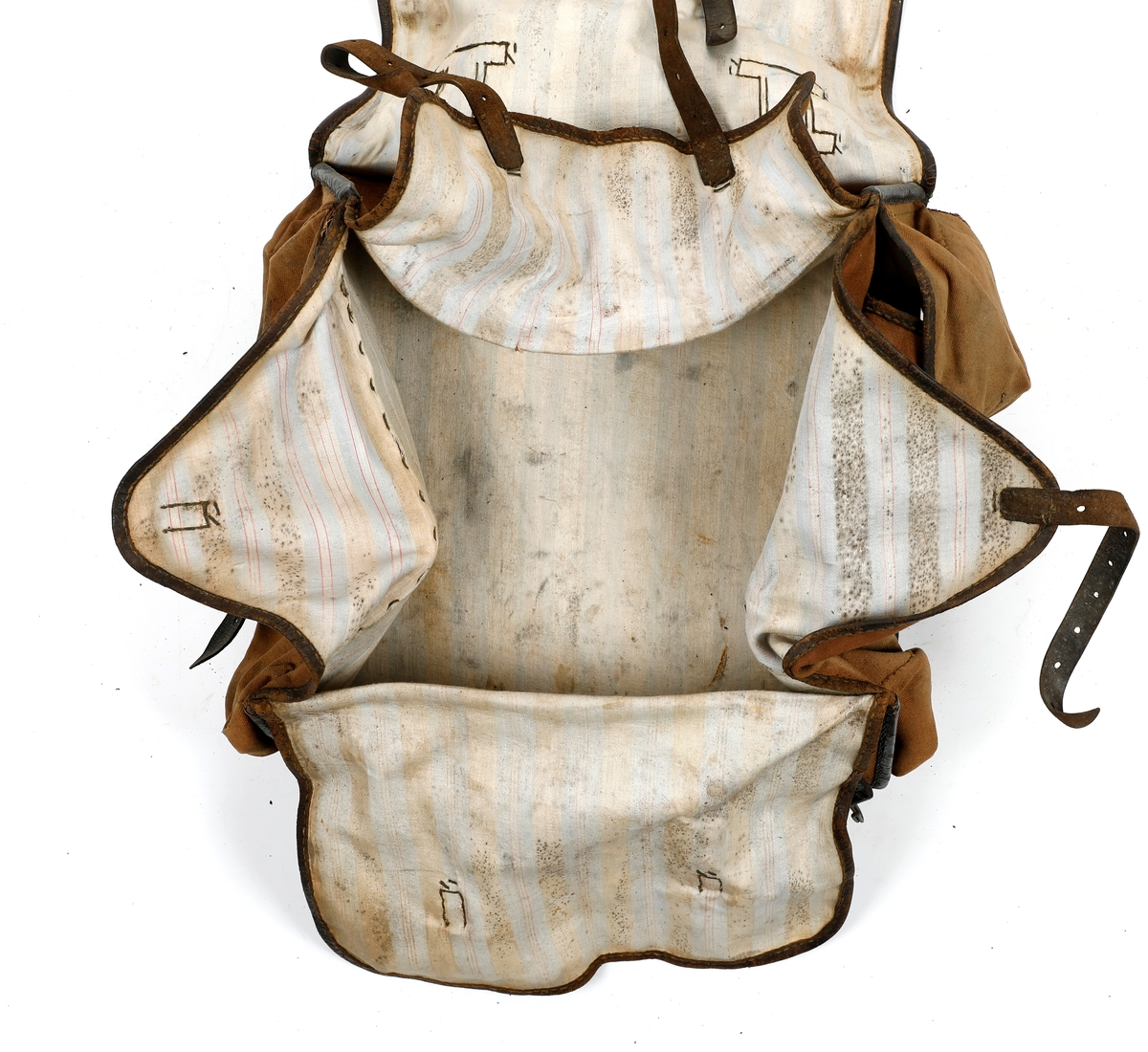 Militærransel i tekstil med kantet med lær. Lommer på hver side av ranselen. Foret med tekstil i bomull. Skulderreimer i læs, hvorav en kan festes til en metallspenne og den andre til en hekte. To doble smøystole på toppen av ranselen. Under lokket er det fire klaffer, to reimer i lær på ytre klaff og en reim på indre klaffer, som som festes til metallspenner. Ranselen er misformet.