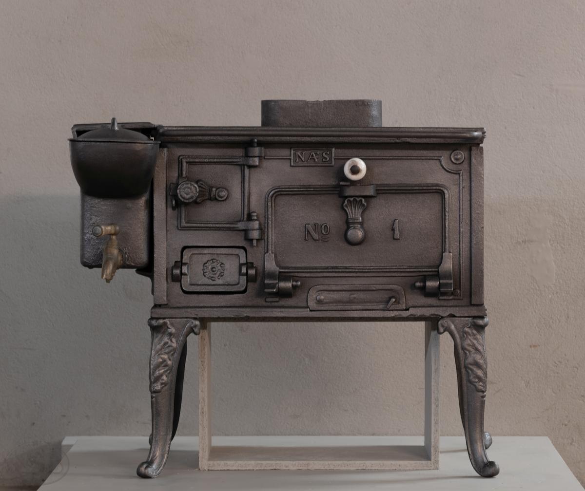 Rektangulær komfyr med  to kokehull på toppen og vanntank på siden. Ovnen har også eget rom for steking med luke i fronten på ovnen. Ovnen er frittstående med fire bein og røkrør i bakant.