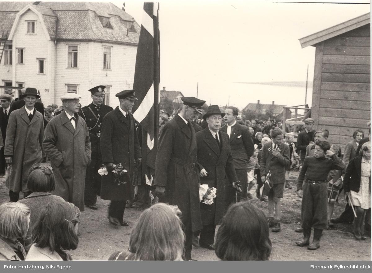Kong Haakon VII på besøk i Vadsø i 1946. Kong Haakon går først i et tog. Til høyre side går fylkesmann Hans Julius Gabrielsen. Mange mennesker har kommet til stede for å se på kongen. Vadsø sykehus (kysthospitalet) i bakgrunnen. Se også bildene 264-267.