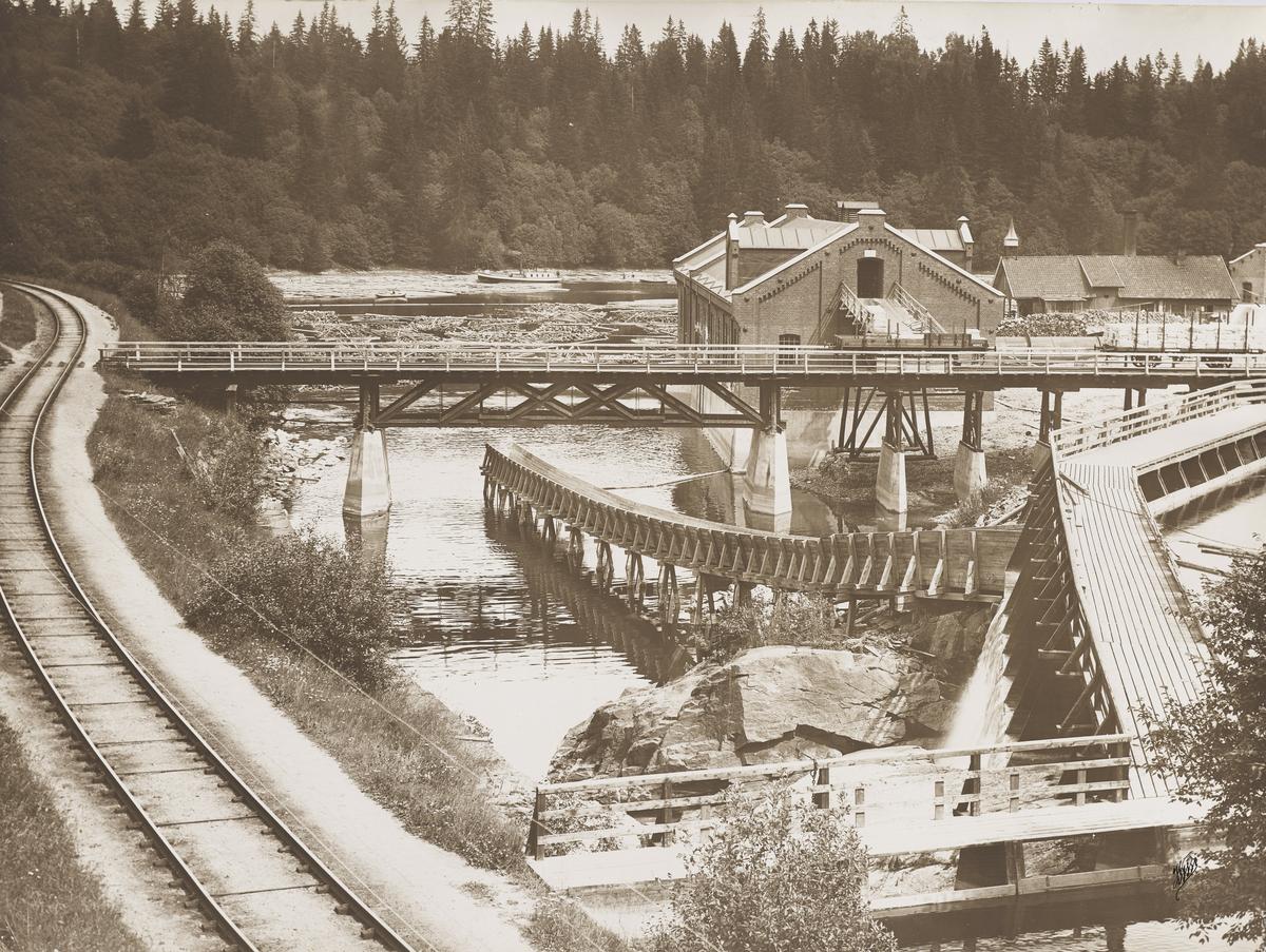 Bilde av såkalte Mago D, også kalt Bårlidalen Tresliperi. Nå brukt til kraftverk, eid og driftet av Hafslund siden 1993, da de kjøpte flere kraftverk fra MEV. Ligger i Andelva, hvor Vorma og Andelva møtes. Tømmer og slepebåt sees på vannet i bakgrunnen. Fløtere og arbeidere jobber med tømmeret.