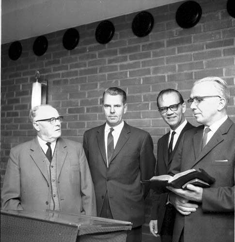Fyra män i mörka kostymer står uppradade runt ett talarbord. En man, Robert Svensson, håller två böcker i handen, eventuellt en bibel och en psalmbok. Intill honom står Olof Nilsson.