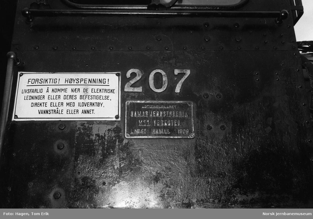 Fabrikk- og nummerskilt på damplokomotiv 21e 207 utenfor lokomotivstallen på Hamar