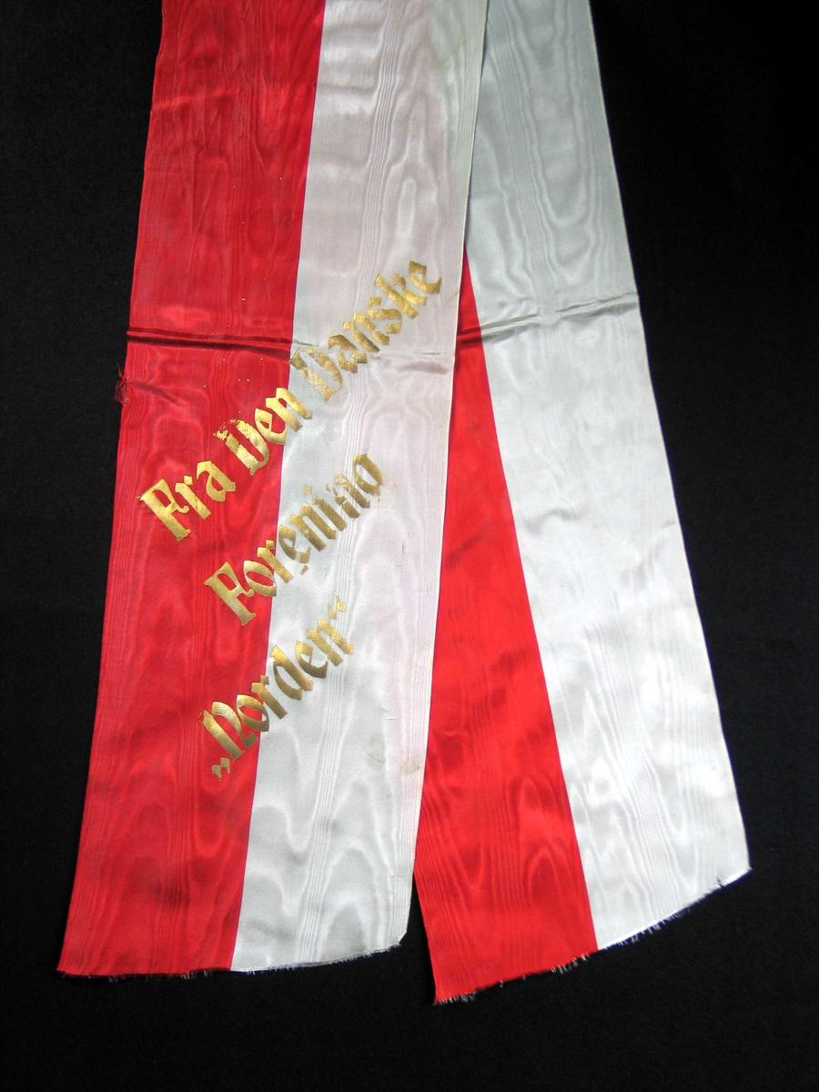 Begravelsessløyfe i rød og hvit silke med tekst i gull.