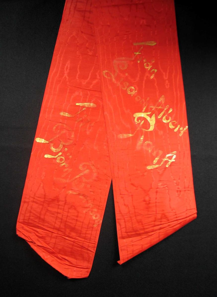 Begravelsessløyfe i rød mønstret silke med tekst i gull.