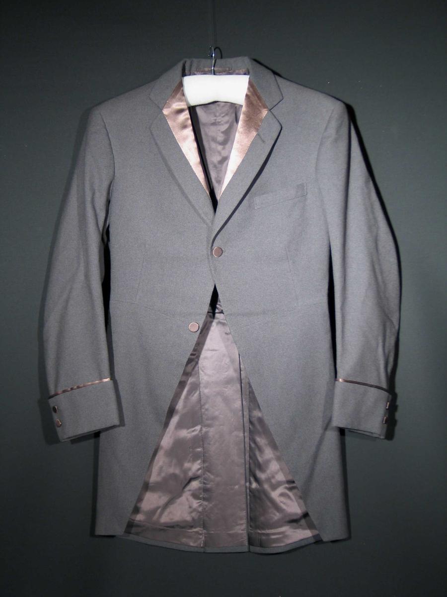 Grå sjakett med blanke slag og splitt bak. Den har mansjetter med to trekte silkeknapper, to knapper i front og to bak. Silkebesetning på slag og mansjetter. Gråbrunt silkefor.