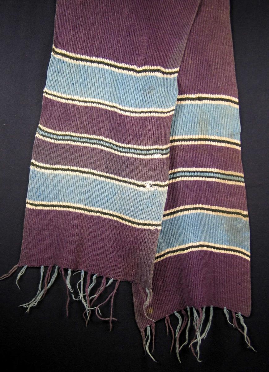 Strikket stripete ullskjerf der hovedfargen er lilla. Frynsene er påsatt med rennesnare.
