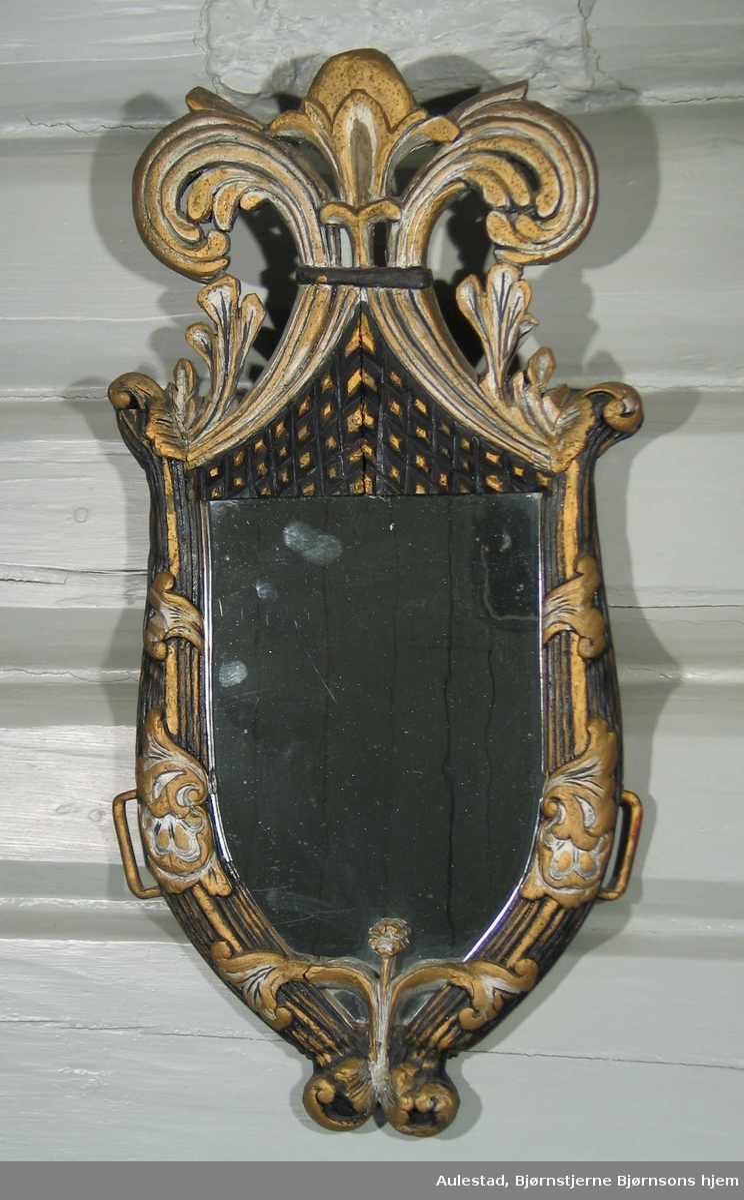 Speil innfattet bogtre. Bogtreet er rikt utskåret. Svart bunnfarge dekorert i gull og sølv. Kraftig toppstykke satt inn mellom bogtreet.
