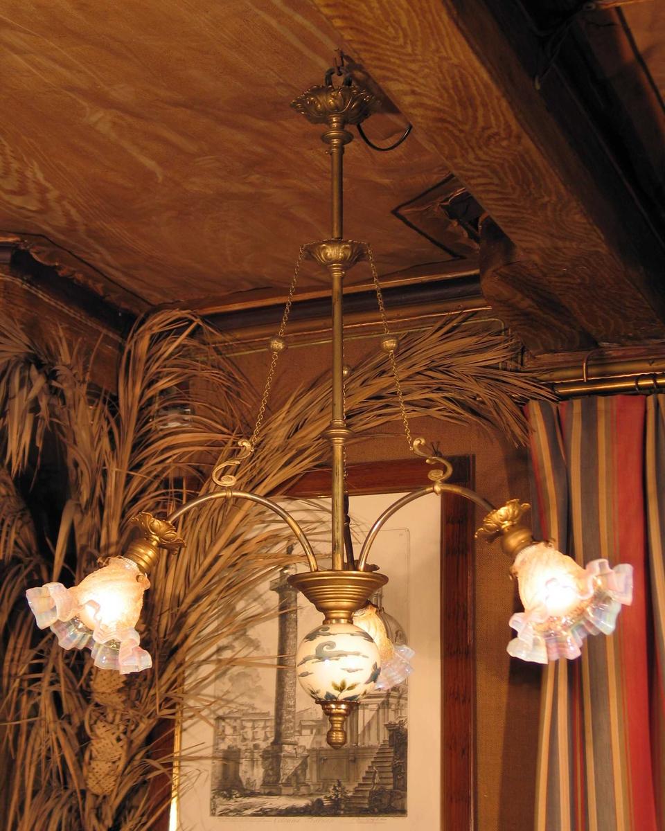 Taklampe med en rosett øverst og en lenger nede der tre kjettinger er festet. Disse går ut til hver sin arm med et s-formet feste. De tre glasskjermene er bølgeformet ytterst og har perlemorfarge. Sentrert under en porselenskule med malt fuglemotiv.