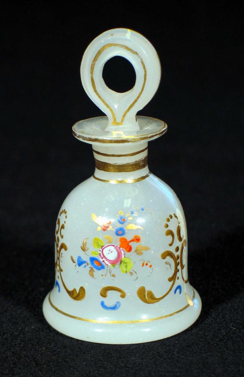 Klokkeformet flakong i melkehvitt glass. Den har  gull- og blomsterdekor. Løkkeformet propp.