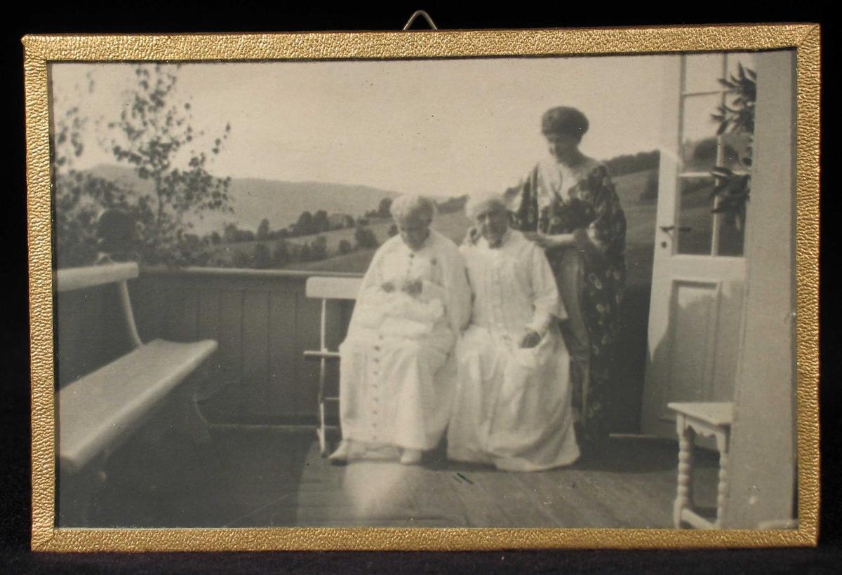 Tre kvinner på en veranda, to en benk og ei stående bak.