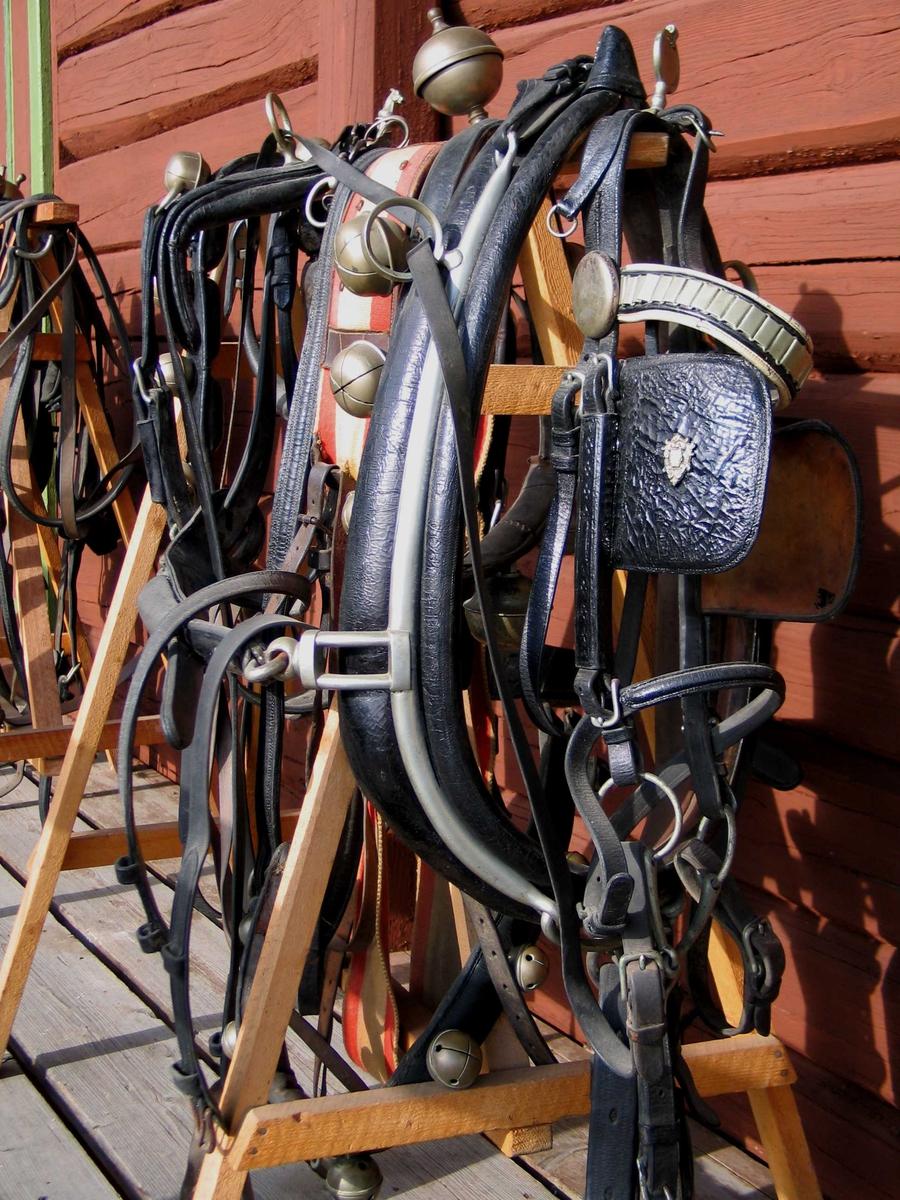 """Seletøy med hodelag, bogring og dombjeller. Skylappene er dekorert med et metallornament, mens hodelaget har metallbord og en oval """"medaljong"""" øverst. Lengre bak et støpt hestehode."""
