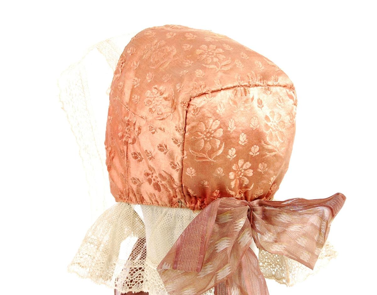 Rosa silkelue med bredt pannestykke og glatt nakkestykke med avrundede hjørner.Lua har en bred påsydd blondekant og silkesløyfe på haka og midt bak. Fôret er av bomull med rosa rutemønster. Påsydd hekte nederst midt bak. Tråd for å feste håret med midt bak. Blondet er av kniplet lintråd, tyllblonde innerst, kniplingsbård ytterst. Knytebånd til hake av hjemmevevet lin. Blonden har midtfold midt foran, er glatt langs ansiktet og er foldelagt bak.